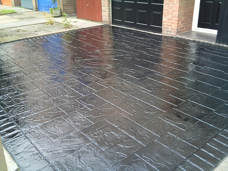 black driveway finished with imprinted concrete